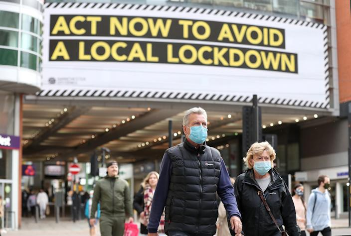 People wearing face masks walk past a advertisement on Market Street in Manchester, as the city is waiting to find out if the region will be placed into the Very High category with tier 3 lockdown restrictions to curb the spread of coronavirus. (Photo by Martin Rickett/PA Images via Getty Images)