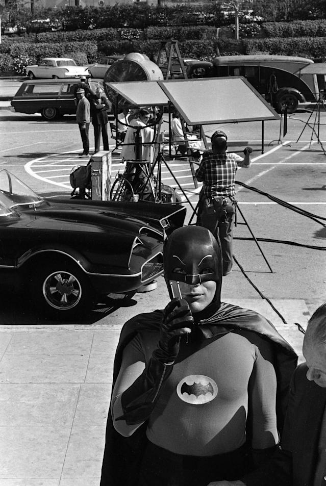 "<p>Adam West, star of the television series ""Batman,"" stands beside the Batmobile and shows off his ""Bat Radio,"" on the Hollywood set for the series during filming of an episode, March 18, 1966. (Photo: AP) </p>"