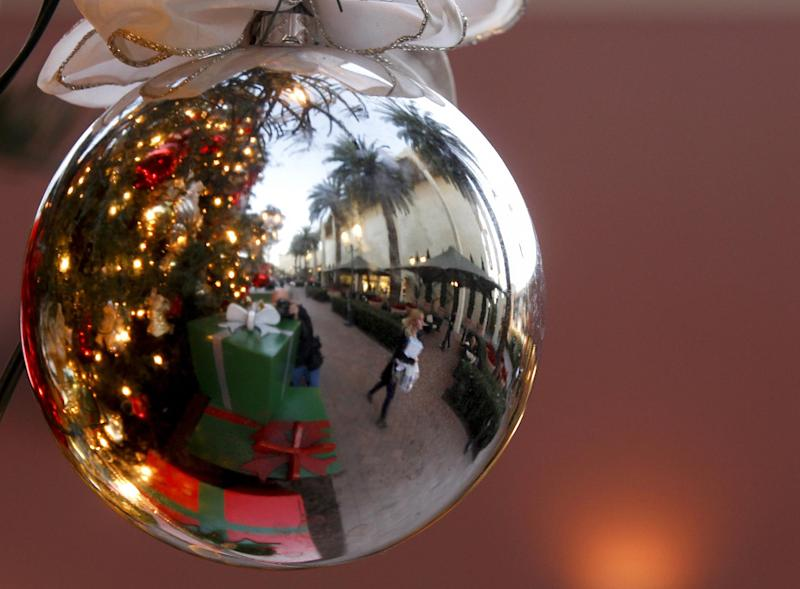 In this Thursday, Dec. 20, 2012, photo, a holiday shoppers reflected in a ornament handing from a large Christmas tree at Fashion Island shopping center in Newport Beach, Calif. Thursday, Dec. 20, 2012. U.S. holiday retail sales this year are the weakest since 2008, after a shopping season disrupted by storms and rising uncertainty among consumers.  A report out Tuesday that tracks spending, called MasterCard Advisors SpendingPulse, says holiday sales increased 0.7 percent. Analysts had expected sales to grow 3 to 4 percent. (AP Photo/Chris Carlson)