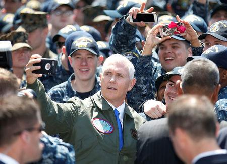U.S. Vice President Mike Pence takes selfie photo with U.S service members as he visits the USS Ronald Reagan, a Nimitz-class nuclear-powered super carrier, at the U.S. naval base in Yokosuka, south of Tokyo, Japan April 19, 2017. REUTERS/Kim Kyung-Hoon