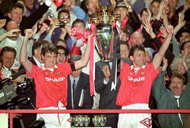 Manchester United players Steve Bruce, left, and Bryan Robson lift the Premier League trophy at the end of the competition's inaugural season in 1993