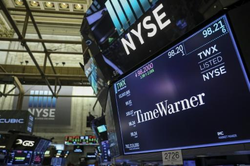 A logo and trading information for Time Warner is seen on a monitor on the floor of the New York Stock Exchange (NYSE), on June 13, 2018