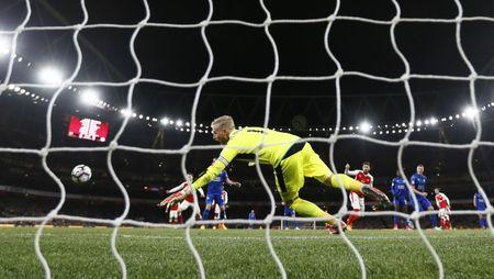 Leicester City's Robert Huth scores an own goal and the first goal for Arsenal
