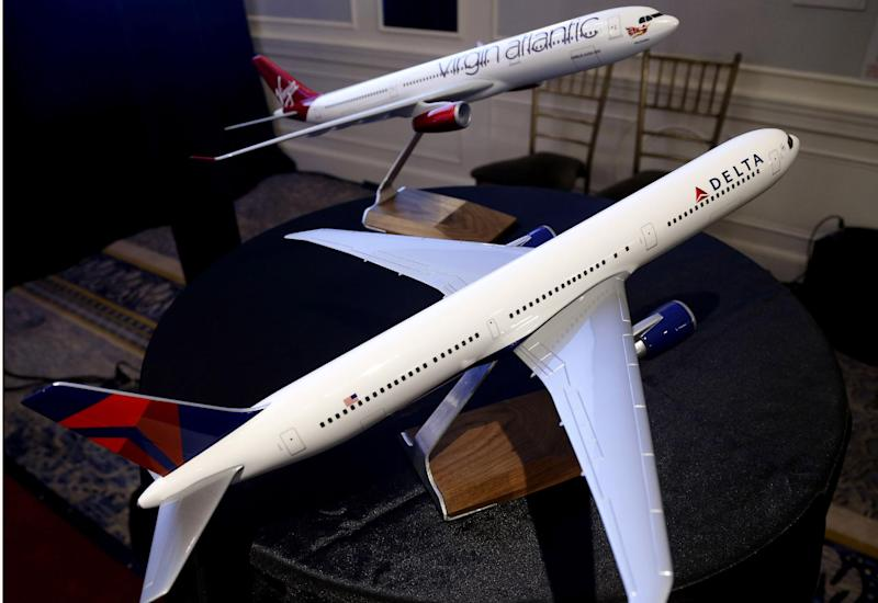 Model planes bearing the logos of Delta Airlines and Virgin Atlantic are displayed during a news conference in New York, Tuesday, Dec. 11, 2012. Delta Air Lines said it will buy almost half of Virgin Atlantic for $360 million as it tries to catch up to rivals in the lucrative New York-to-London travel market. (AP Photo/Seth Wenig)