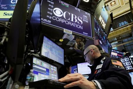FILE PHOTO: A trader works below the CBS Corporation logo on the floor of the New York Stock Exchange shortly after the opening bell in New York