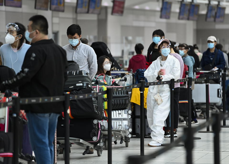 People line up and check in for an international flight at Pearson International airport during the COVID-19 pandemic in Toronto on Wednesday, Oct. 14, 2020.  (Nathan Denette/The Canadian Press via AP)