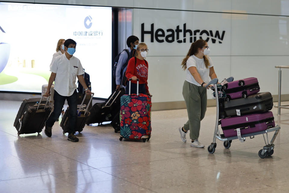 Passengers wearing PPE (personal protective equipment) arrive at Terminal 2 of Heathrow airport, west London on May 22, 2020. (Photo by Tolga Akmen / AFP) (Photo by TOLGA AKMEN/AFP via Getty Images)