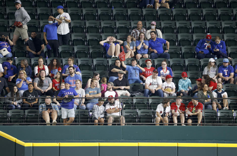 Fans in the outfield seats wait between innings in the baseball game between the Texas Rangers and the Los Angeles Angels during the ninth inning Tuesday, April 27, 2021, in Arlington, Texas. (AP Photo/Ron Jenkins)