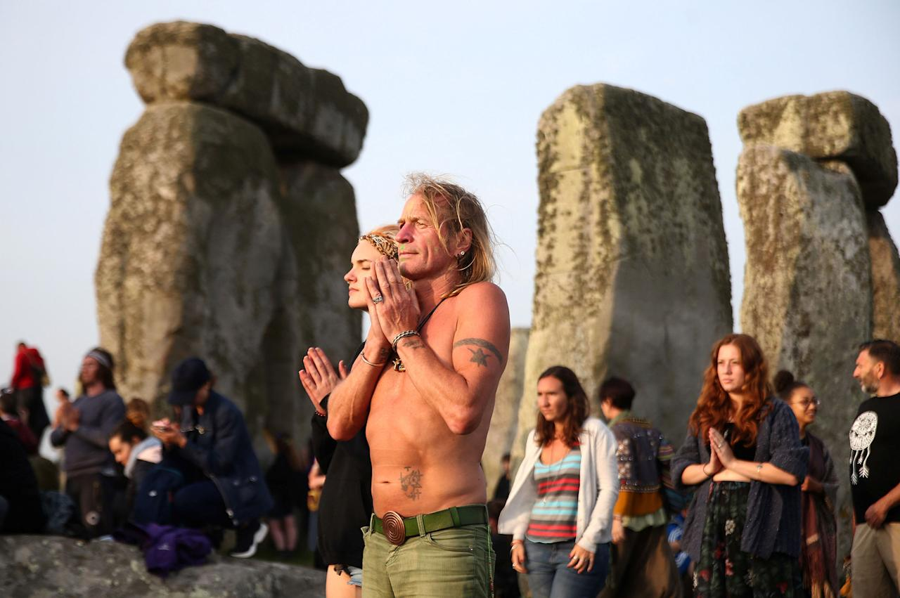 <p>People watch the sun rise on the Stonehenge monument on the summer solstice near Amesbury, Britain, June 21, 2017. (Photo: Neil Hall/Reuters) </p>