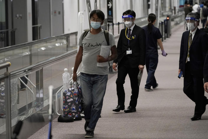 Yuki Kitazumi, a Japanese freelance journalist detained by security forces in Myanmar in mid-April and accused of spreading fake news criticizing the military coup, walks as he arrives at Narita International Airport, in Narita, east of Tokyo. (AP Photo/Eugene Hoshiko)