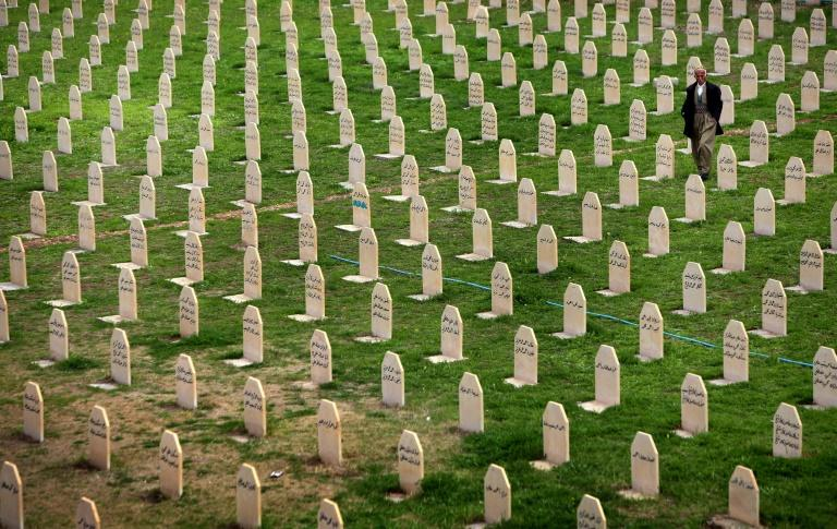 In this file picture taken on March 16, 2014 an Iraqi Kurd man walks past tomb stones as he visits a grave yard for the victims of a gas attack by former Iraqi dictator Saddam Hussein in 1988 in the Kurdish town of Halabja