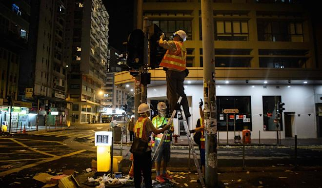 Workers repair smashed traffic lights after a protest. Photo: AFP