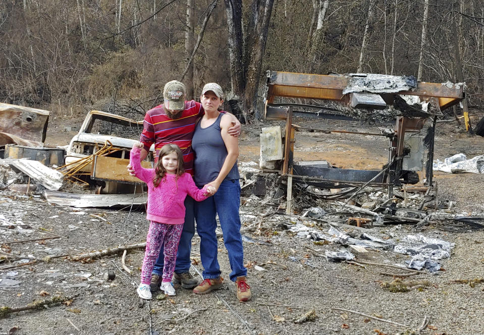 In this photo provided by Tye and Melynda Small, they are seen standing with their 5-year-old daughter, Madalyn, in front of the ruins of their home in Otis, Oregon after the Echo Mountain Fire swept through, burning nearly 300 homes, in September, 2020. The Smalls had to take Madalyn back to their property to help her understand why they couldn't go home. Oregon's unprecedented wildfire season last fall burned 4,000 homes and more than 1 million acres in areas that aren't normally associated with wildfire. Experts say the 2020 wildfire season in Oregon was a taste of what lies ahead as climate change makes blazes more likely and more destructive even in wetter, cooler climates like the Pacific Northwest. (Tye and Melynda Small via AP)