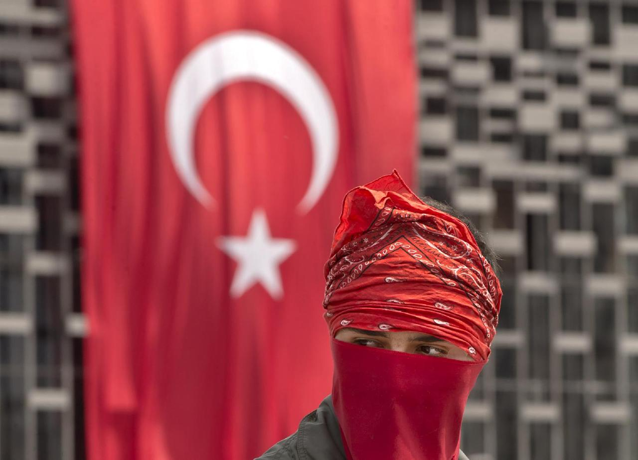 A masked protester is backdropped by a Turkish flag on the edge of Gezi Park, in Istanbul, Turkey, Wednesday, June 12, 2013. Riot police fired tear gas, water cannon and rubber bullets in day-long clashes that lasted into the early hours Wednesday, battling protesters who have been occupying Istanbul's central Taksim Square and its adjacent Gezi Park in the country's most severe anti-government protests in decades.(AP Photo/Vadim Ghirda)