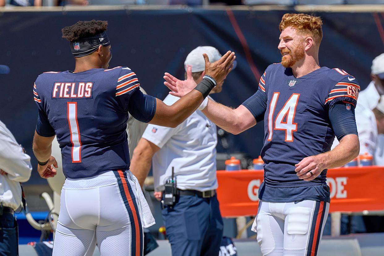 CHICAGO, IL - AUGUST 14: Chicago Bears quarterback Andy Dalton (14) shake hands with Chicago Bears quarterback Justin Fields (1) during a preseason game between the Chicago Bears and the Miami Dolphins on August 14, 2021 at Soldier Field in Chicago, IL. (Photo by Robin Alam/Icon Sportswire via Getty Images)
