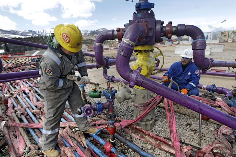 In this March 29, 2013 photo, workers tend to a well head during a hydraulic fracturing operation at an Encana Oil & Gas (USA) Inc. gas well outside Rifle, in western Colorado. Technology created an energy revolution over the past decade, but Old Energy is winning. Oil companies big and small have used technology to find a bounty of oil and natural gas so large that worries about running out have melted away. (AP Photo/Brennan Linsley)
