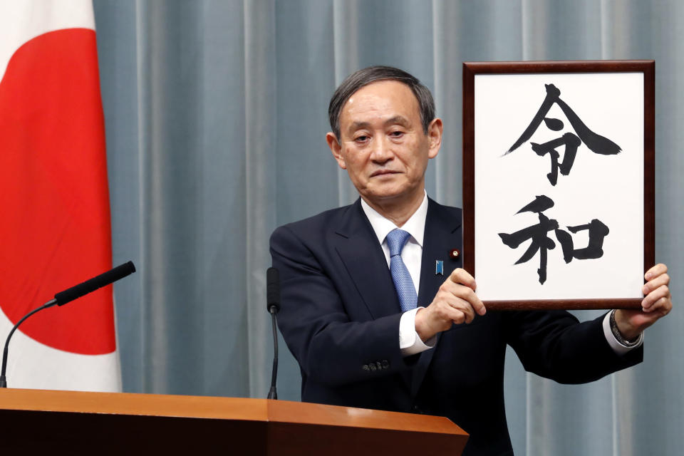 """FILE - In this April 1, 2019, file photo, Japan's Chief Cabinet Secretary Yoshihide Suga unveils the name of new era """"Reiwa"""" at the prime minister's office in Tokyo. Japan's Parliament elected Suga as prime minister Wednesday, Sept. 16, 2020, replacing long-serving leader Shinzo Abe with his right-hand man. (AP Photo/Eugene Hoshiko, File)"""