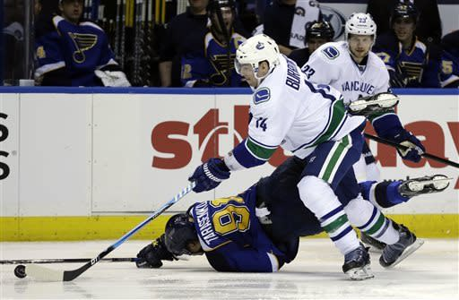 St. Louis Blues' Vladimir Tarasenko, of Russia, takes a tumble as Vancouver Canucks' Alex Burrows (14) chases after a loose puck as teammate Alexander Edler (23), of Sweden, watches during the second period of an NHL hockey game Tuesday, April 16, 2013, in St. Louis. (AP Photo/Jeff Roberson)