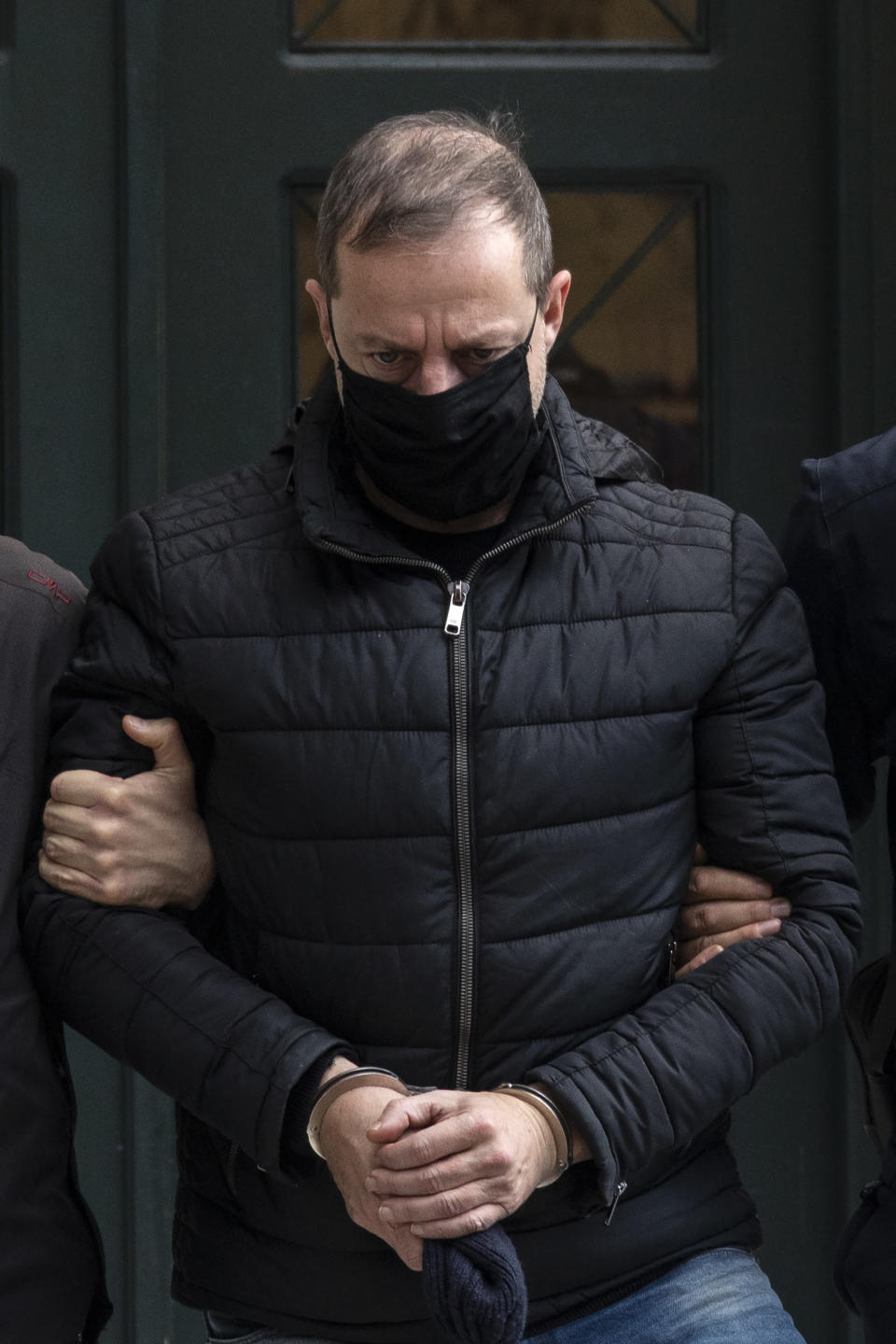 Handcuffed actor and director Dimitris Lignadis, leaves a magistrate's office in Athens, Sunday, Feb. 21, 2021. Lignadis, 56, the former artistic director of Greece's National Theatre, has been arrested on rape charges, police say. (AP Photo/Yorgos Karahalis)