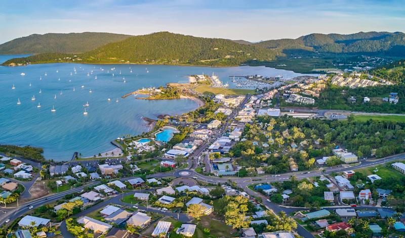 Panorama aerial view of the main street of Airlie Beach with Pioneer Bay and boats in background.