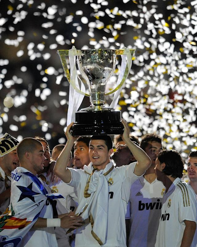 MADRID, SPAIN - MAY 13: Cristiano Ronaldo of Real Madrid CF holds up the La Liga trophy as he celebrates with team-mates after the La Liga match between Real Madrid CF and RCD Mallorca at Estadio Santiago Bernabeu on May 13, 2012 in Madrid, Spain. (Photo by Denis Doyle/Getty Images)