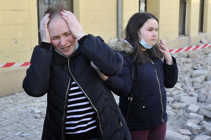 A woman reacts next to buildings damaged in an earthquake in Petrinja, Croatia, Tuesday, Dec. 29, 2020. A strong earthquake has hit central Croatia and caused major damage and at least one death and 20 injuries in a town southeast of the capital Zagreb. (AP Photo)