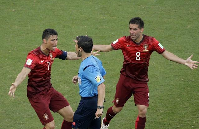 Portugal's Cristiano Ronaldo, left, and Portugal's Joao Moutinho protest to referee Milorad Mazic from Serbia during the group G World Cup soccer match between Germany and Portugal at the Arena Fonte Nova in Salvador, Brazil, Monday, June 16, 2014. (AP Photo/Christophe Ena)