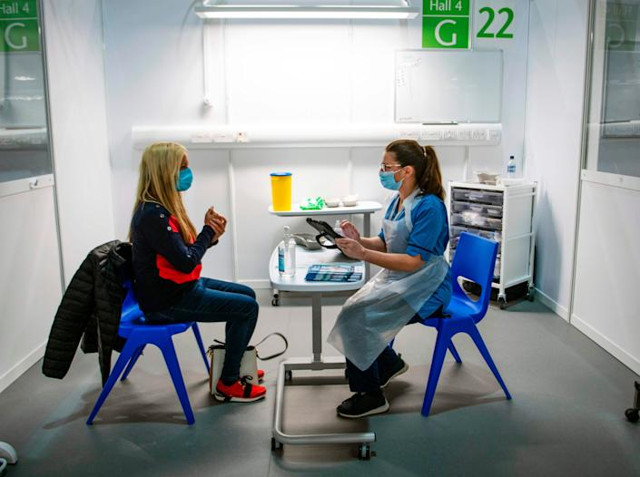Immunisation Nurse Debbie Briody (R) fills in forms prior to administering the Pfizer/BioNtech Covid-19 vaccine to Staff Nurse Amanda Thompson at the NHS Louisa Jordan temporary hospital at the SEC Campus in Glasgow (AFP via Getty Images)