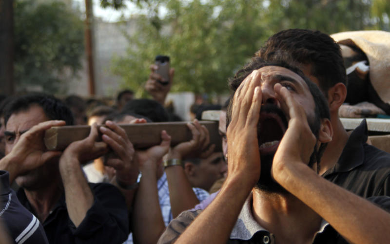 A Syrian man chants slogans during the funeral of 29 year-old Free Syrian Army fighter, Husain Al-Ali, who was killed during clashes in Aleppo, in the town of Marea on the outskirts of  Aleppo city, Syria, Thursday, Aug. 9, 2012. (AP Photo/ Khalil Hamra)
