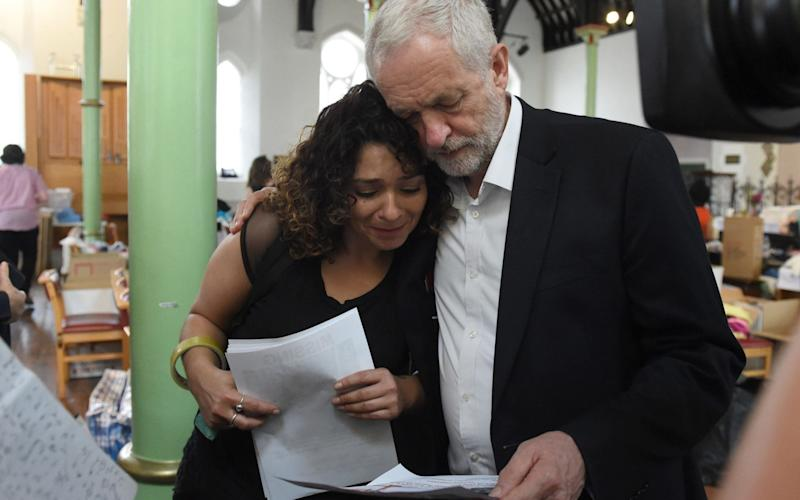 Jeremy Corbyn, the Labour leader, comforts a resident - PA