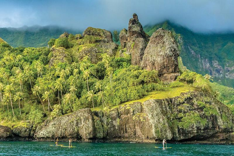 Paddleboarding at Fatu Hiva in the Marquesas Archipelago, French Polynesia—one of the trips hosted by Lindblad Expeditions, whose itineraries are newly 100% carbon-neutral.
