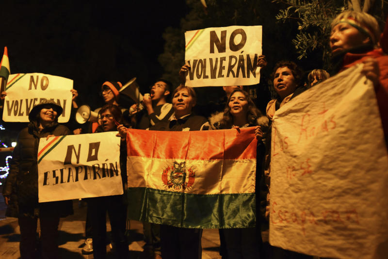 People protest outside the residence of Mexico's ambassador with flags and signs, against officials of the previous Bolivian government who have taken refuge inside the residence in La Paz, Bolivia, late Friday, Dec. 27. 2019. (AP Photo/Luis Gandarillas)
