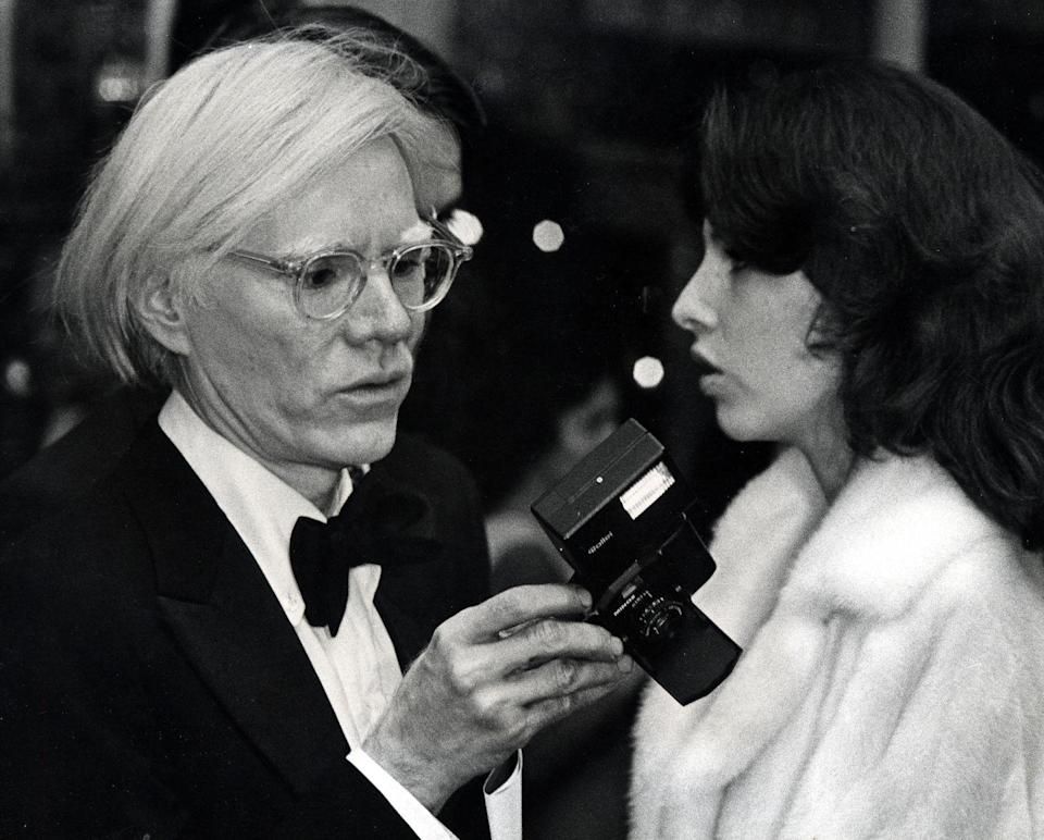 <p>Andy Warhol attends the premiere for <em>A Star is Born </em>in 1976. The famed artist and photographer brought his camera along for the fashionable event. </p>