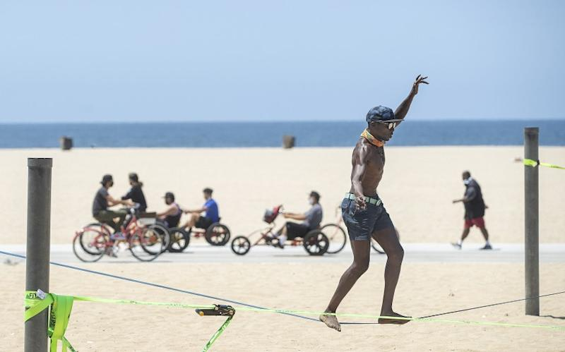 SANTA MONICA, CA - JUNE 29: Jacob Laiser, 38, of Venice, balances on a slack line, while working out at Santa Monica Beach on Monday, June 29, 2020 in Santa Monica, CA. L.A. County is expected to reach 100,000 cases of coronavirus.