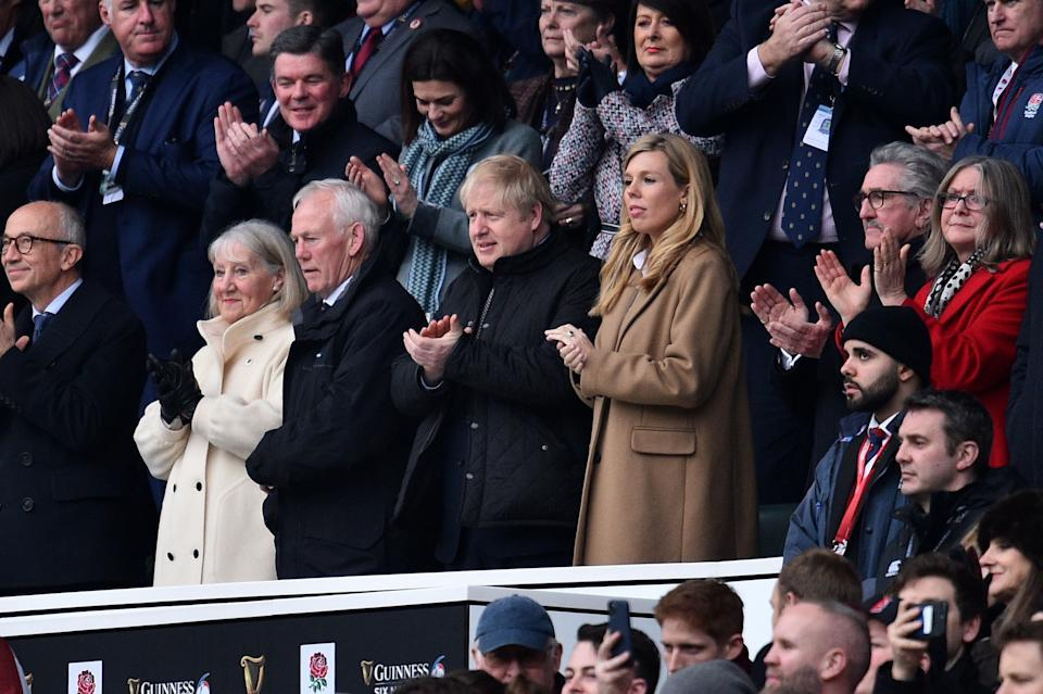 Britain's Prime Minister Boris Johnson (L) with his partner Carrie Symonds attend the Six Nations international rugby union match between England and Wales at the Twickenham, west London, on March 7, 2020. (Photo by Glyn KIRK / AFP) (Photo by GLYN KIRK/AFP via Getty Images)