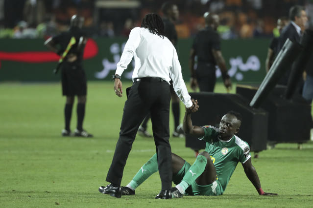 Senegal's head coach Aliou Cisse helps Senegal's Sadio Mane to Stans up end the African Cup of Nations final soccer match between Algeria and Senegal in Cairo International stadium in Cairo, Egypt, Friday, July 19, 2019. Algeria won 1-0. (AP Photo/Hassan Ammar)