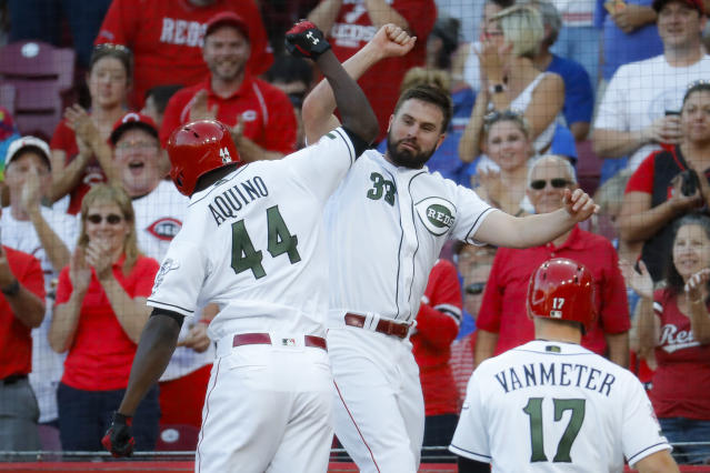 Cincinnati Reds' Aristides Aquino (44) celebrates with Jesse Winker (33) after hitting a two-run home run off Chicago Cubs starting pitcher Yu Darvish in the second inning of a baseball game, Friday, Aug. 9, 2019, in Cincinnati. (AP Photo/John Minchillo)