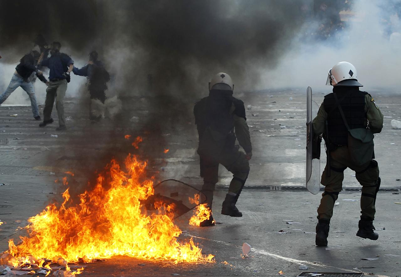 Riot policemen react as a bin caught fire after being hit by a petrol bomb as protester throw stones during rioting in central Athens, Thursday, Oct. 20, 2011. A protester died and dozens were injured during an anti-austerity demonstration that turned violent in the Greek capital, hours before lawmakers were to vote on deeply unpopular new cutbacks demanded by creditors to keep Greece financial solvent.(AP Photo/Petros Giannakouris)