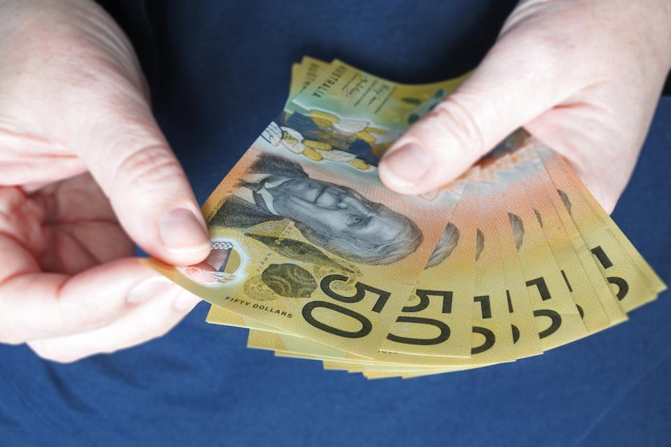 POV (Point of view) of young adult Australian woman counting cash of Australian dollar banknotes close up.