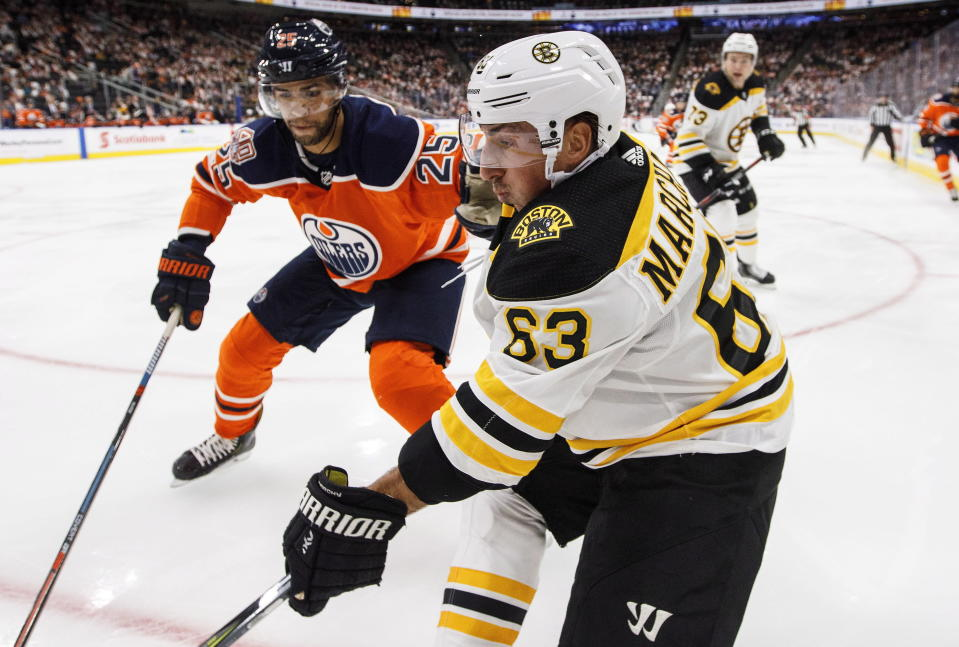 Boston Bruins' Brad Marchand (63) battles for the puck with Edmonton Oilers' Darnell Nurse (25) during second period NHL hockey action in Edmonton, Alberta, Thursday Oct. 18, 2018. (Jason Franson/The Canadian Press via AP)