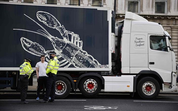 Police officers talk to a driver working in the shellfish industry who brought his truck to central London to protest against post-Brexit red tape and coronavirus restrictions -  AFP
