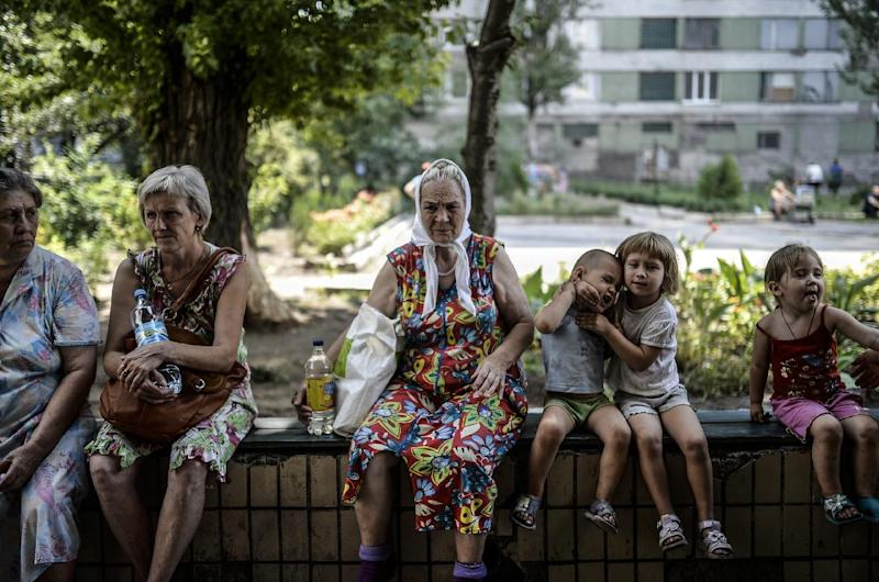 Refugees wait in front of a hostel building ran by pro-Russian rebels in the centre of Donetsk, on August 4, 2014