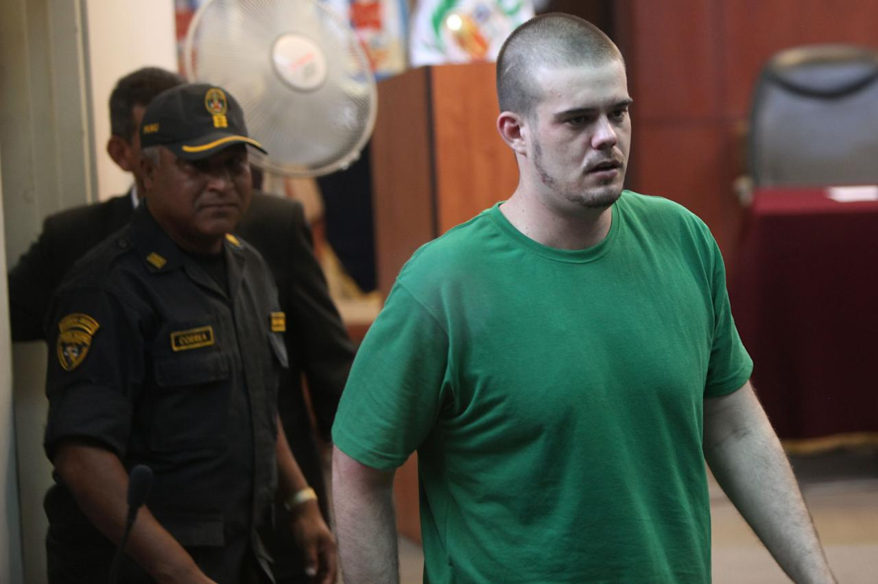 Joran van der Sloot, right, arrives to the courtroom for his sentence at San Pedro prison in Lima, Peru, Friday Jan. 13, 2012. Van der Sloot will be sentenced Friday for the 2010 murder of Stephany Flores, a young woman he met at a Lima casino. Prosecutors have asked for a 30-year sentence for first-degree murder and theft. (AP Photo/Karel Navarro)