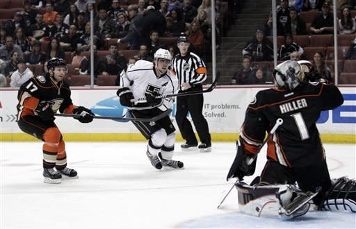 Los Angeles Kings center Anze Kopitar, center, of Slovenia, watches his goal against Anaheim Ducks goalie Jonas Hiller, right, as Ducks' Lubomir Visnovsky looks on in the first period of an NHL hockey game in Anaheim, Calif., Friday, March 16, 2012. (AP Photo/Jae C. Hong)