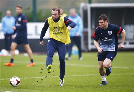 England national soccer team player Rooney kicks the ball as teammate Milner chases during a team training session in London Colney