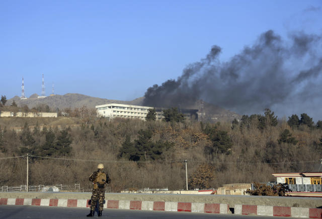 <p>An Afghan security official stand guard as black smoke rises from the Intercontinental Hotel after an attack in Kabul, Afghanistan, Sunday, Jan. 21, 2018. Gunmen stormed the hotel and sett off a 12-hour gun battle with security forces that continued into Sunday morning, as frantic guests tried to escape from fourth and fifth-floor windows. (Photo: Rahmat Gul/AP) </p>