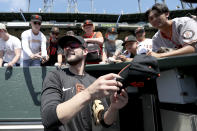 San Francisco Giants' Kris Bryant gives autographs to fans prior to a baseball game against the Houston Astros in San Francisco, Sunday, Aug. 1, 2021. (AP Photo/Jed Jacobsohn)