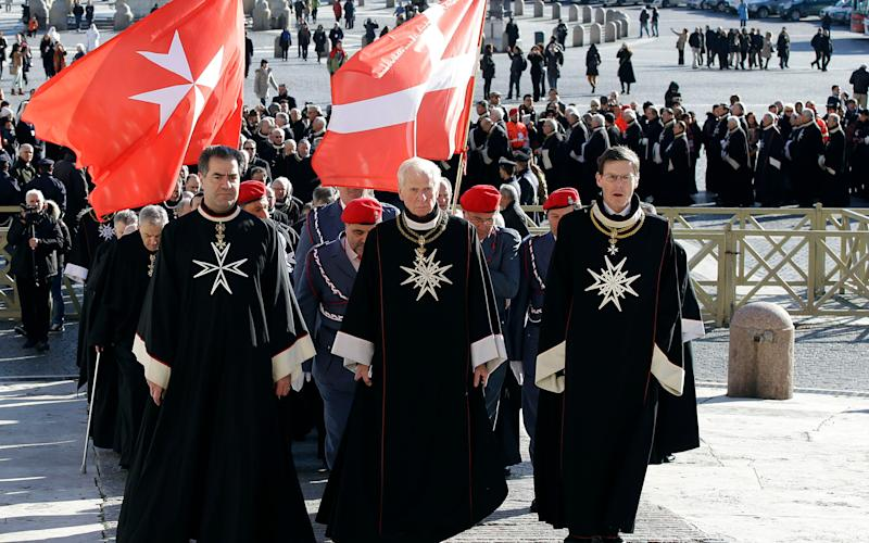Members of the Knights of Malta walk in procession towards St. Peter's Basilica during a celebration to mark the 900th anniversary of the Order in 2013. The order traces its history to the 11th century with the establishment of an infirmary in Jerusalem that cared for people making pilgrimages to the Holy Land. - Credit: Gregorio Borgia/AP