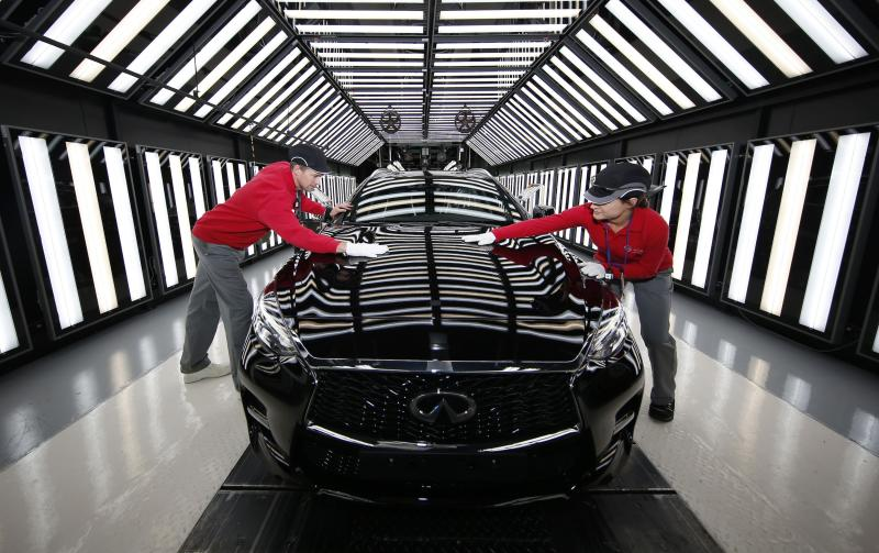 """Workers at Nissan's plant in Sunderland on the production line for the Infiniti Q30 """"active compact"""" vehicle, the first major new brand of car to be manufactured in Britain for 23 years."""