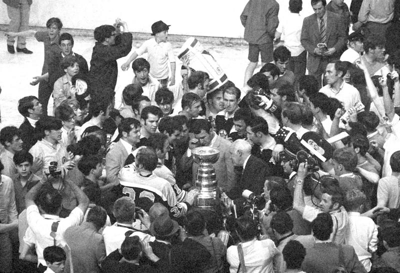 FILE - In this May 10, 1970, file photo, Boston Bruins defenseman Teddy Green, center, wipes away tears as he is surrounded by teammates after they beat the St. Louis Blues in overtime to win the Stanley Cup in Boston, Mass. Green was out of action for the season after being injured in a stick swinging fray in a pre-season exhibition game. (AP Photo/File)